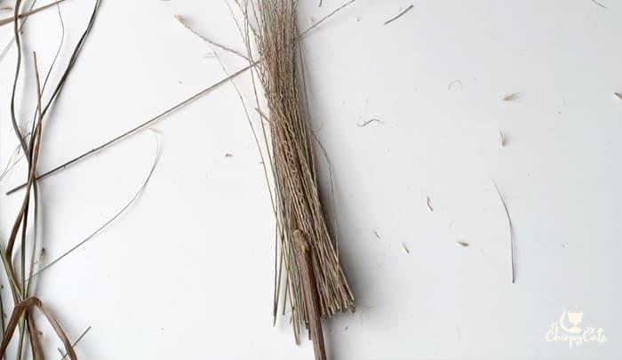 using grass and cat vine sticks to make mini witches broom