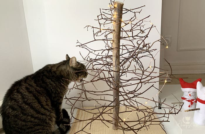 cat biting at branches of DIY cat christmas tree made from vine branches